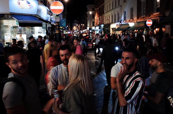 Revelers socialize on Old Compton Street in the hospitality and nightlife hotspot of Soho in London on July 18, 2020. (Photo: NurPhoto via Getty Images)