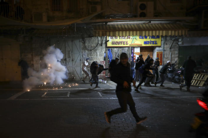 Palestinians run away as a stun grenades are fired by Israeli police during clashes at Damascus Gate just outside Jerusalem's Old City, Thursday, April. 22, 2021. Palestinians clashed with Israeli police over restrictions on Ramadan gatherings ahead of a planned march by Lahava, a Jewish extremist group, to the area later on Thursday amid heightened tensions in the city. (AP Photo/Mahmoud Illean)