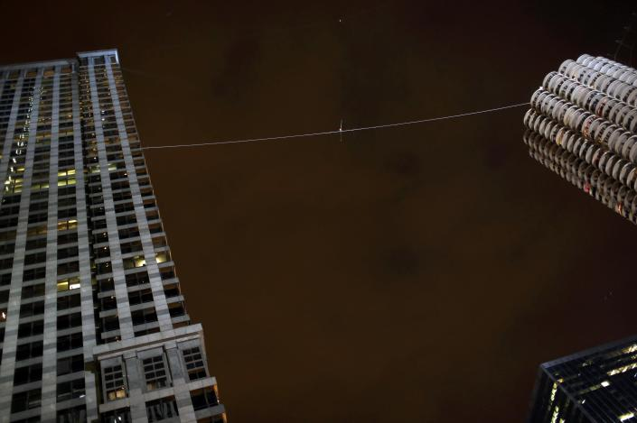 Daredevil Nik Wallenda walks along a tightrope between two skyscrapers suspended 500 feet (152.4 meters) above the Chicago River in Chicago, Illinois, November 2, 2014. (REUTERS/John Gress)