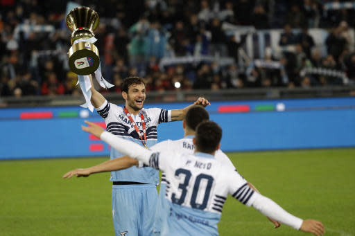 Lazio's Marco Parolo, top left, holds up the Italian Cup trophy at the end of the final match between Lazio and Atalanta, at the Rome Olympic stadium, Wednesday, May 15, 2019. (AP Photo/Alessandra Tarantino)