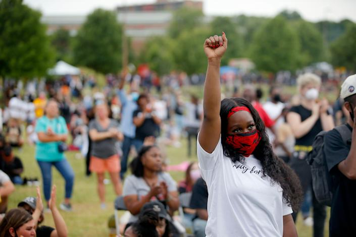 A woman raises her fist as she watches a speaker during a Juneteenth celebration in Tulsa, Oklahoma.