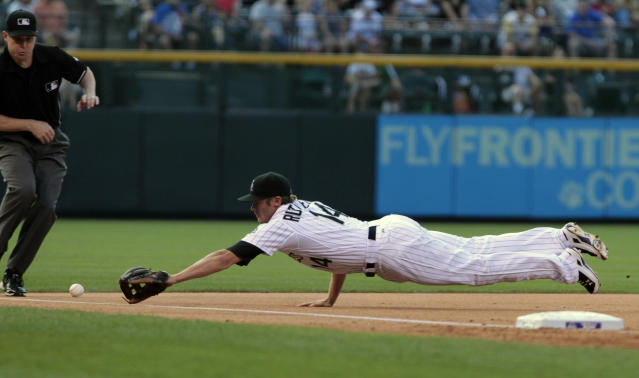 Colorado Rockies' Josh Rutledge (14) dives for Milwaukee Brewers' Aramis Ramirez's single that scored Brewers' Jonathan Lucroy and Carlos Gomez in the first inning of a baseball game in Denver, Friday, June 20, 2014. (AP Photo/Joe Mahoney)