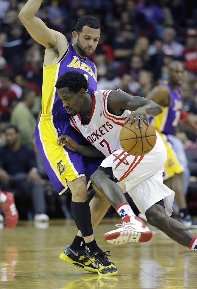 Houston Rockets' Patrick Beverley (2) drives around Los Angeles Lakers' Jordan Farmar (1) during the second quarter of an NBA basketball game Thursday, Nov. 7, 2013, in Houston. (AP Photo/David J. Phillip)