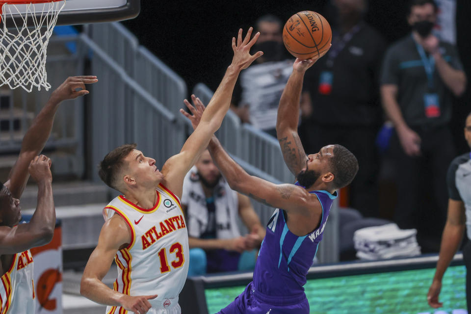Charlotte Hornets guard Brad Wanamaker, right, shoots over Atlanta Hawks guard Bogdan Bogdanovic, left, during the second quarter of an NBA basketball game in Charlotte, N.C., Sunday, April 11, 2021. (AP Photo/Nell Redmond)