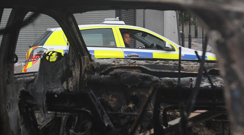A police officer looks at the remains of a burned out police car in Tottenham, north London Sunday Aug. 7, 2011after a demonstration against the death of a local man turned violent and cars and shops were set ablaze. One police officer was hospitalized and seven others were injured during riots after a north London suburb exploded in anger Saturday night after a gathering to protest the Thursday shooting by police of the 29-year-old.   (AP Photo/ Lewis Whyld/PA Wire)  UNITED KINGDOM OUT