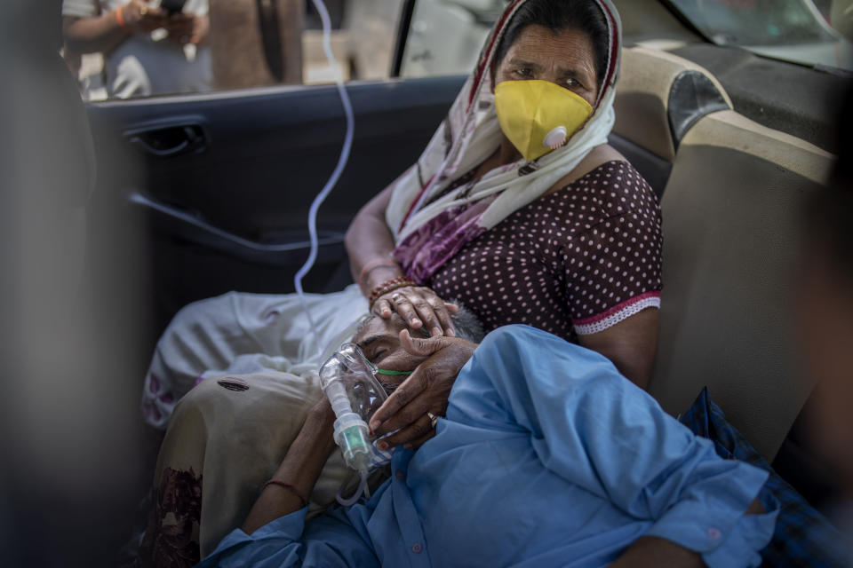A patient breathes with the help of oxygen provided by a Gurdwara, Sikh place of worship, inside a car in New Delhi, India, Saturday, April 24, 2021. India's medical oxygen shortage has become so dire that this gurdwara began offering free breathing sessions with shared tanks to COVID-19 patients waiting for a hospital bed. They arrive in their cars, on foot or in three-wheeled taxis, desperate for a mask and tube attached to the precious oxygen tanks outside the gurdwara in a neighborhood outside New Delhi. (AP Photo/Altaf Qadri)