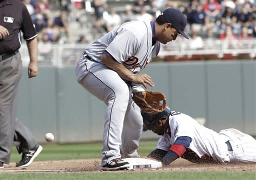 Detroit Tigers third baseman Miguel Cabrera, left, can't handle the throw as Minnesota Twins' Alexi Casilla steals third in the fifth inning of a baseball game Sunday, Sept. 30, 2012 in Minneapolis. (AP Photo/Jim Mone)