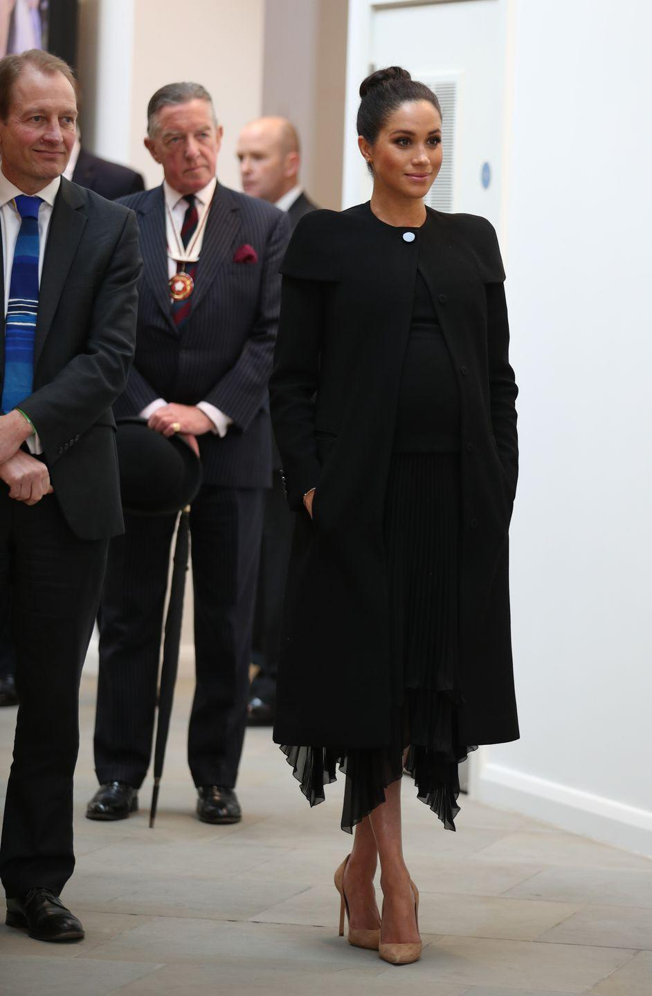 <p>Meghan looked chic in a black Givenchy coat, which she previously wore for the Remembrance Day Service in November, while visiting the Association of Commonwealth Universities. The Duchess completed the look with a black pleated chiffon dress and nude pumps. </p>