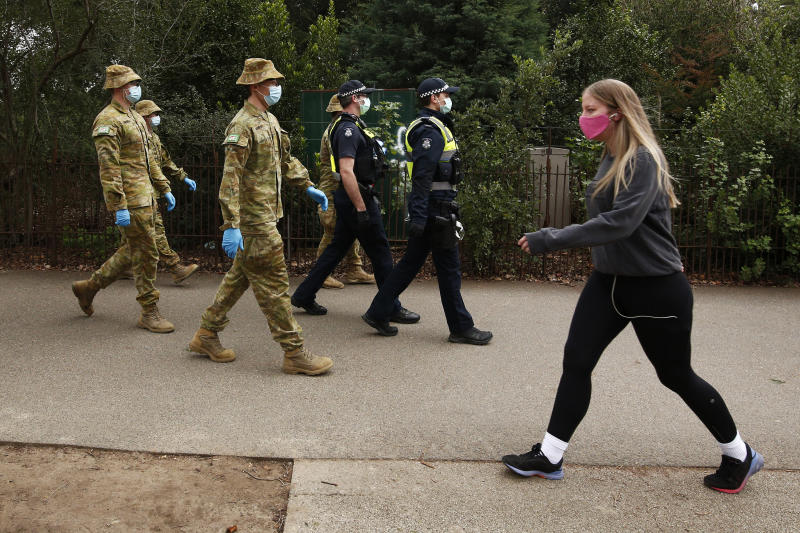 ADF personnel and Victorian police officers are seen patrolling the Tan walking track in Melbourne in late July. Source: AAP