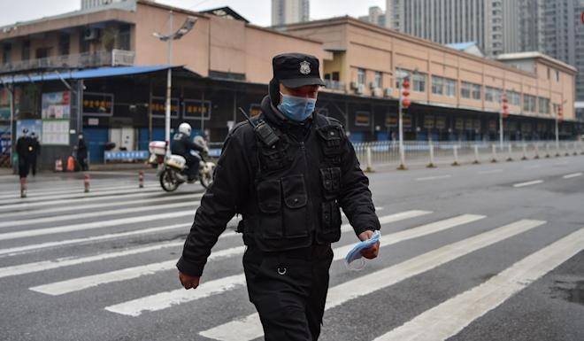 A police officer walks in front of Huanan Seafood Wholesale market in Wuhan on Friday. The death toll in China's viral outbreak has risen to 26, with the number of confirmed cases also leaping to 875. Photo: AFP