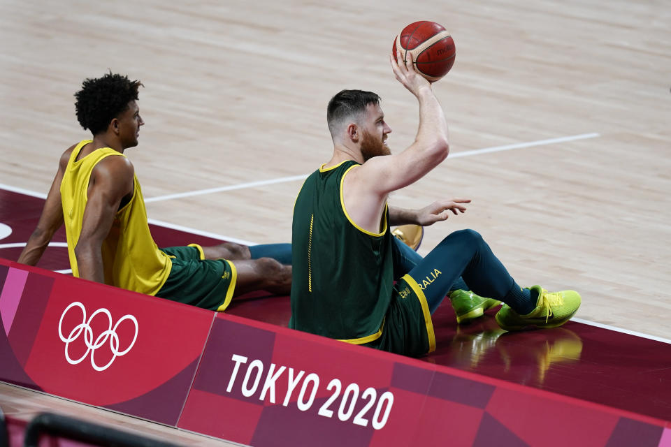 Australia's Aron Baynes, right, and Matisse Thybulle sit on the court during a men's basketball practice at the 2020 Summer Olympics, Friday, July 23, 2021, in Saitama, Japan. (AP Photo/Charlie Neibergall)