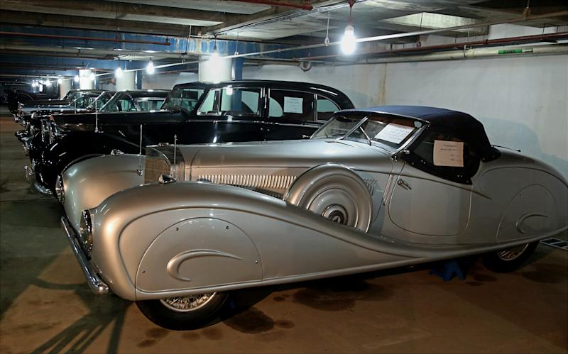 In this Sunday, Jan. 7, 2018 photo, a collection of luxury classic cars used by the Hashemite monarchy from 1921 until 1958, including a 1936 Mercedes Benz, foreground, that was a gift from Adolf Hitler and others that belonged to Uday, the notoriously brutal playboy son of Saddam Hussein, are stored in a garage for safe-keeping in Baghdad, Iraq. The promise of better days after Iraq's victory against the Islamic State group is rekindling interest in classic cars. (AP Photo/Karim Kadim)