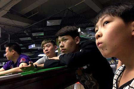 Students watch live Ding Junhui playing against Mark Selby on the television during the Betfred World Snooker Championship, at World Snooker College in Beijing, China, April 28, 2017. REUTERS/Thomas Suen