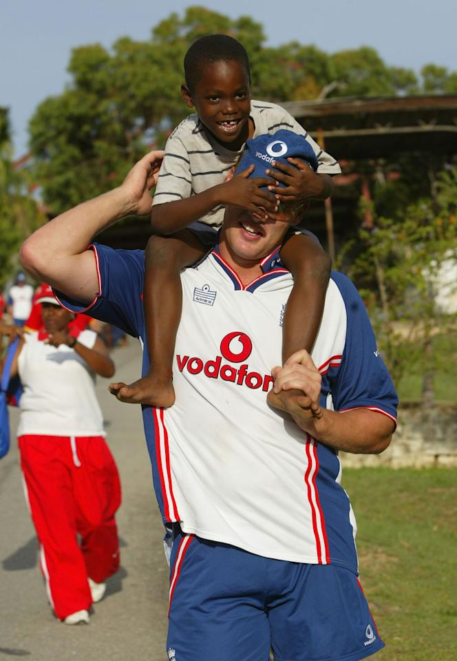 PORT OF SPAIN, TRINIDAD - APRIL 21:  Andrew Flintoff of England gives a lift to a child during a visit to the local orphanage on April 21, 2004 in Port of Spain, Trinidad.  (Photo by Tom Shaw/Getty Images)