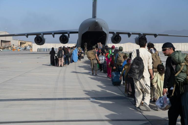 This handout photo courtesy ot the US Air Force shows passengers waiting to board a US air transport at Hamid Karzai International Airport (HKIA), Afghanistan, August 24, 2021 (AFP/Donald R. ALLEN)