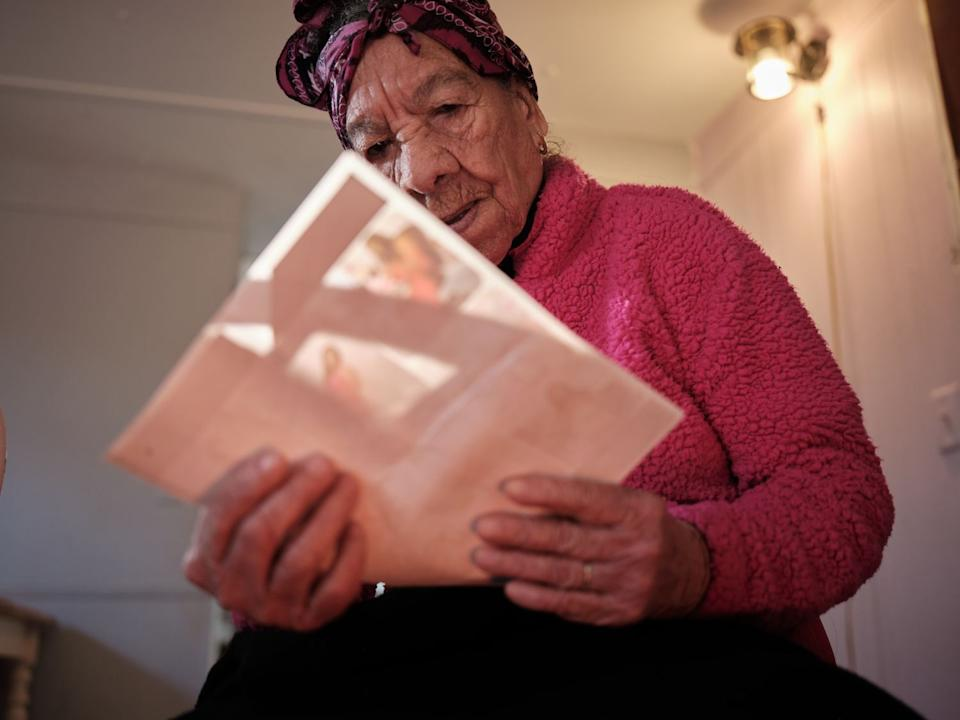 Doña Amalia reads some of the family's immigration paperwork.