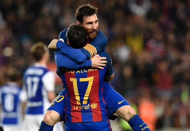 Barcelona's Paco Alcacer (bottom) celebrates with teammate Lionel Messi during their match against Real Sociedad at the Camp Nou stadium in Barcelona on April 15, 2017 (AFP Photo/LLUIS GENE)