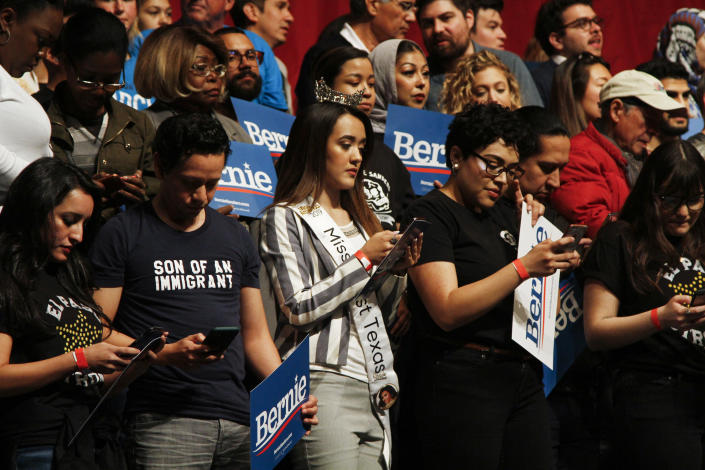 Supporters of Democratic presidential candidate Sen. Bernie Sanders I-Vt. text a phone number to find their closet polling place at a campaign event in El Paso, Texas, Saturday, Feb. 22, 2020. (AP Photo/Cedar Attanasio)
