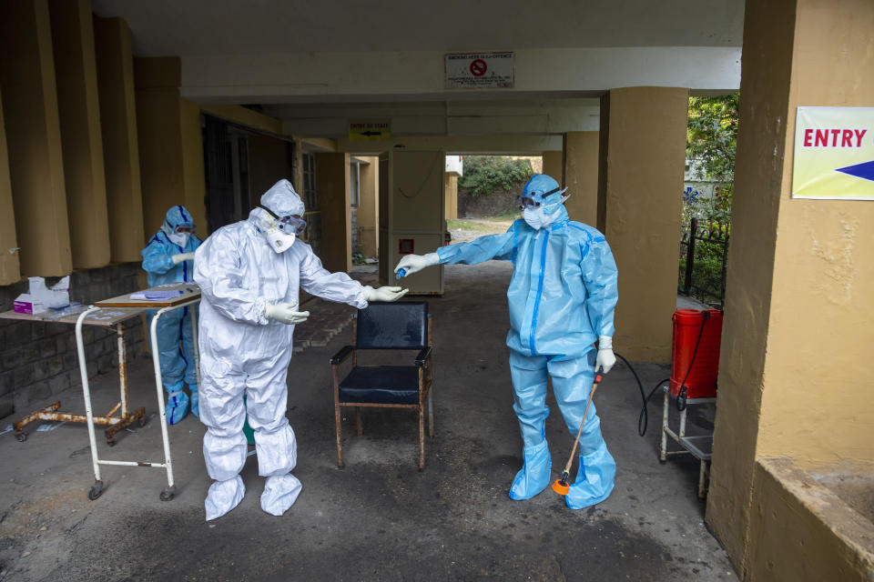 A health officer in protective suit gives hand sanitiser to another at a COVID-19 testing center in Dharmsala, India, Thursday, Oct. 29, 2020. (AP Photo/Ashwini Bhatia)