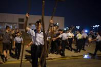 A policeman removes part of a barricade after pro-democracy protesters tried to block a road outside the central government offices in Hong Kong on October 15, 2014 (AFP Photo/Ed Jones)
