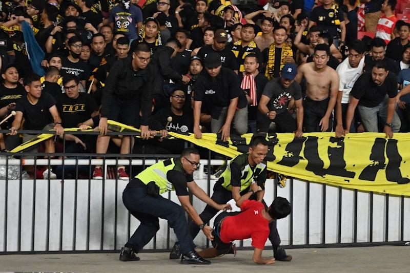Police detain a supporter of Indonesia next to supporters of Malaysia (in black) after an incident during the Fifa World Cup preliminary qualification round 2 at Gelora Bung Karno stadium in Jakarta September 5, 2019. — AFP pic