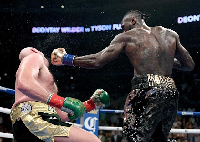 Deontay Wilder knocks Tyson Fury down during their bruising WBC heavyweight title battle in Los Angeles last December (AFP Photo/Harry How)