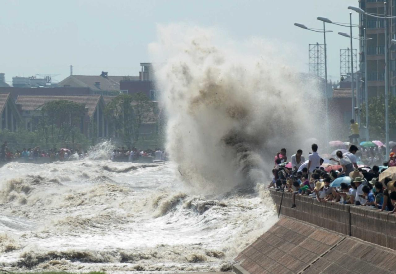 HAINING, CHINA - AUGUST 31:  (CHINA OUT) Spectators are swept by huge waves while watching tides of Qiantang River at a dike on August 31, 2011 in Haining, Zhejiang Province of China. More than 20 spectators were injured by strong tides as the typhoon Nanmadol approached on Wednesday.  (Photo by ChinaFotoPress/Getty Images)