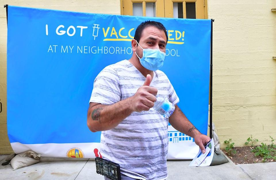 Jorge Montoya gives a thumbs after receiving his first Pfizer Covid-19 vaccine administered by medical assistants from St. John's Well Child and Family Center at Abraham Lincoln High School in Los Angeles.