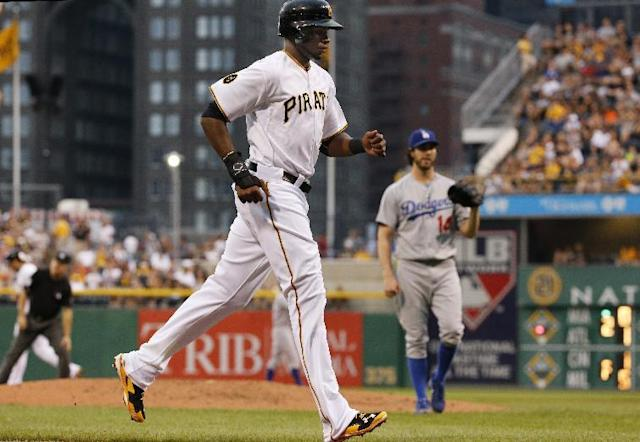 Pittsburgh Pirates' Gregory Polanco, left, is forced home from third on a bases-loaded walk by Los Angeles Dodgers starting pitcher Dan Haren (14) during the first inning of a baseball game in Pittsburgh, Wednesday, July 23, 2014. (AP Photo)