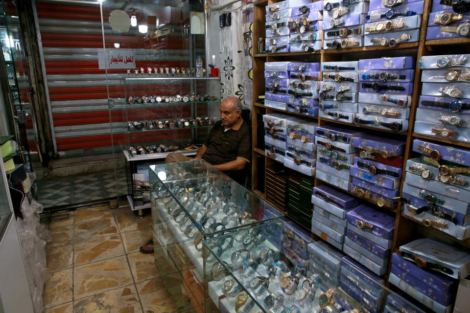 A shop owner waits for customers in Baghdad, Iraq, Tuesday, Oct. 20, 2020. Iraq is in the throes of an unprecedented liquidity crisis, as the cash-strapped state wrestles to pay public sector salaries and import essential goods while oil prices remain dangerously low. (AP Photo/Khalid Mohammed)