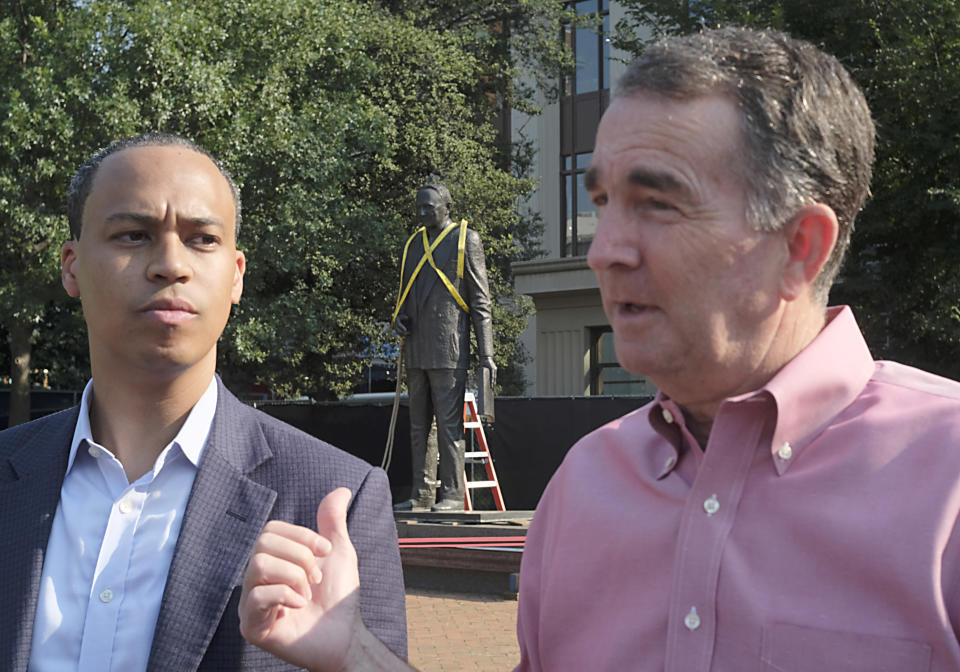 Del. Jay Jones, D-Norfolk, left, and Virginia Governor Ralph Northam, right, make a statement to the media before the statue of Harry F. Byrd, Sr., former Virginia Governor and U. S. Senator, background, was removed from the pedestal in Capitol Square in Richmond, Va. Wednesday, July 7, 2021. The General Assembly approved Jones' bill calling for the removal during the last session. (Bob Brown/Richmond Times-Dispatch via AP)