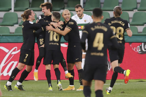 Barcelona's Riqui Puig, second left, celebrates after scoring his side's second goal during the Spanish La Liga soccer match between Elche and Barcelona at the Manuel Martinez Valero stadium in Elche, Spain, Sunday, Jan. 24, 2021. (AP Photo/Alberto Saiz)