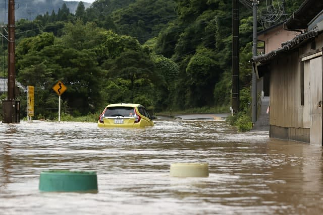 A car is stuck in a flooded road in Yatsushiro (Kyodo News via AP)