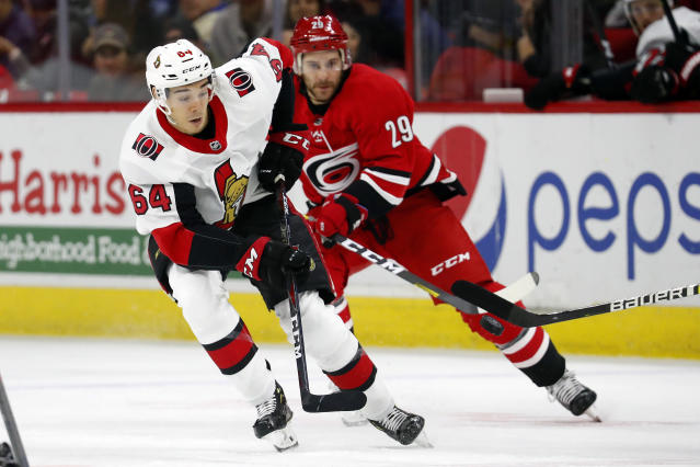 Ottawa Senators' J.C. Beaudin (64) moves the puck in front of Carolina Hurricanes' Brian Gibbons (29) during the first period of an NHL hockey game in Raleigh, N.C., Monday, Nov. 11, 2019. (AP Photo/Karl B DeBlaker)