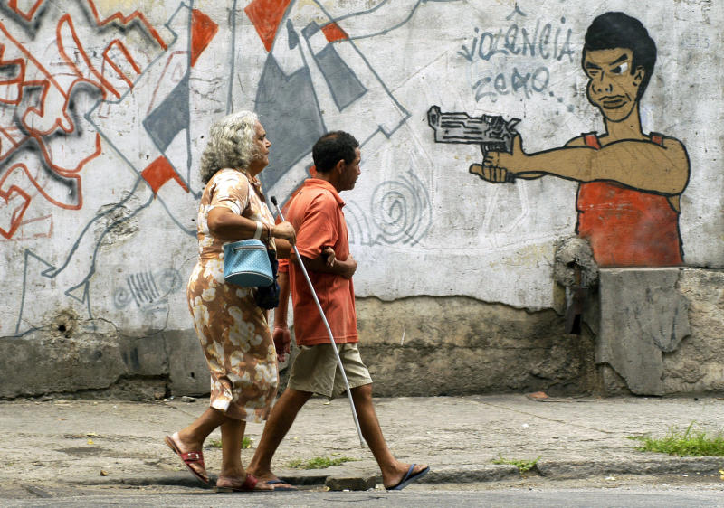 FILE - In this Oct. 22, 2005 file photo, people walk past graffiti in Rio de Janeiro, Brazil, a day before a vote to ban the sale of firearms and ammunition to civilians. Backed by the Roman Catholic church and other powerful forces in the country, one poll a month before the referendum put support at 73 percent. The U.S.-based National Rifle Association worked with activists in Brazil to help defeat it. (AP Photo/Renzo Gostoli, File)