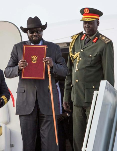 South Sudan's President Salva Kiir holds a copy of the ceasefire and power sharing agreement he signed with rebel chief Riek Machar as he arrives back in the capital Juba on August 6, 2018