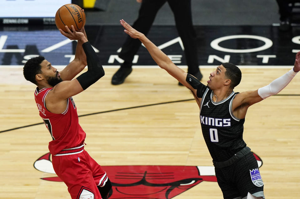 Chicago Bulls guard Garrett Temple, left, shoots against Sacramento Kings guard Tyrese Haliburton during the first half of an NBA basketball game in Chicago, Saturday, Feb. 20, 2021. (AP Photo/Nam Y. Huh)
