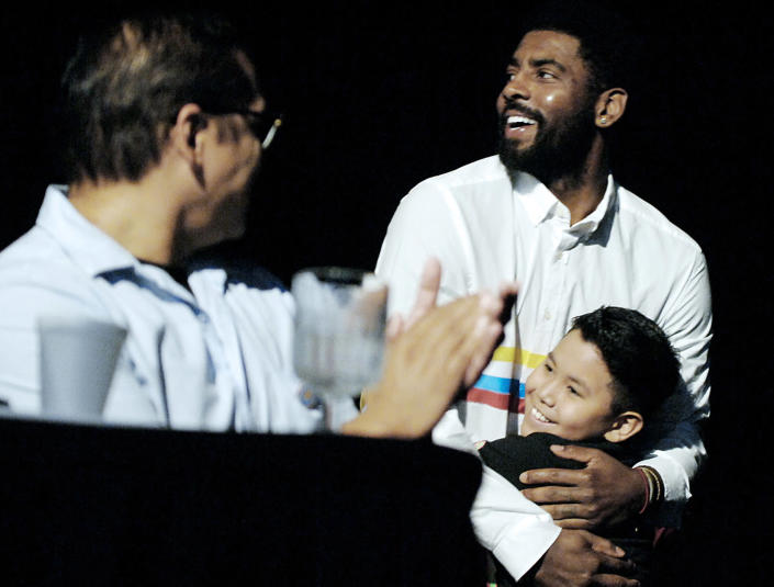 Boston Celtic point guard Kyrie Irving hugs his name sake, Kyrie Irving, 9, of Fort Yates, N.D., during a naming ceremony in his honor, Thursday, Aug. 23, 2018 at the Prairie Knights Casino north of Fort Yates, N.D. on the Standing Rock Sioux Indian Reservation. Irving's mother, Elizabeth Larson, was an enrolled member of the tribe before being adopted as a youngster. Irving was named Little Mountain by the tribe. (Mike McCleary/The Bismarck Tribune via AP)