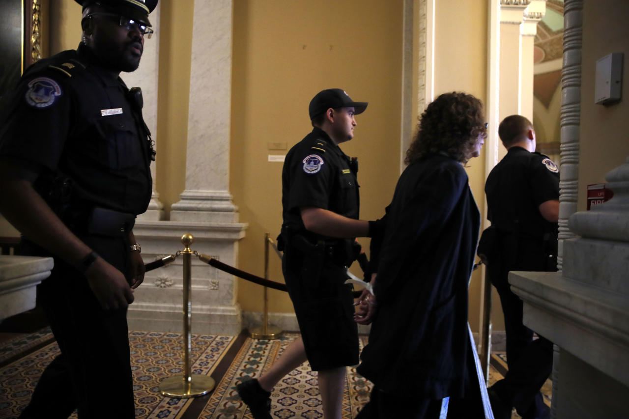 Demonstrators are removed from the Senate Chamber on Capitol Hill in Washington, Tuesday, July 25, 2017, as Republican Senators moved ahead on health care with the goal of erasing much of Barack Obama's law. (AP Photo/Jacquelyn Martin)