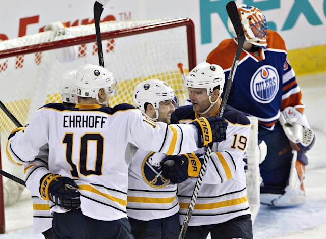 Buffalo Sabres' Torrey Mitchell, left rear, Christian Ehrhoff (10), Cory Conacher and Cody Hodgson (19) celebrate a goal against Edmonton Oilers goalie Ben Scrivens, rear, during the third period of an NHL hockey game Thursday, March 20, 2014, in Edmonton, Alberta. Buffalo won 3-1. (AP Photo/The Canadian Press, Jason Franson)