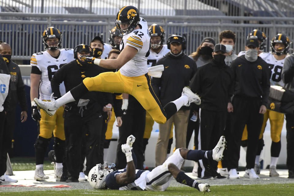Iowa tight end Shaun Beyer (42) hurdles Penn State safety Lamont Wade (38) in the first quarter of an NCAA college football game in State College, Pa., on Saturday, Nov. 21, 2020. (AP Photo/Barry Reeger)