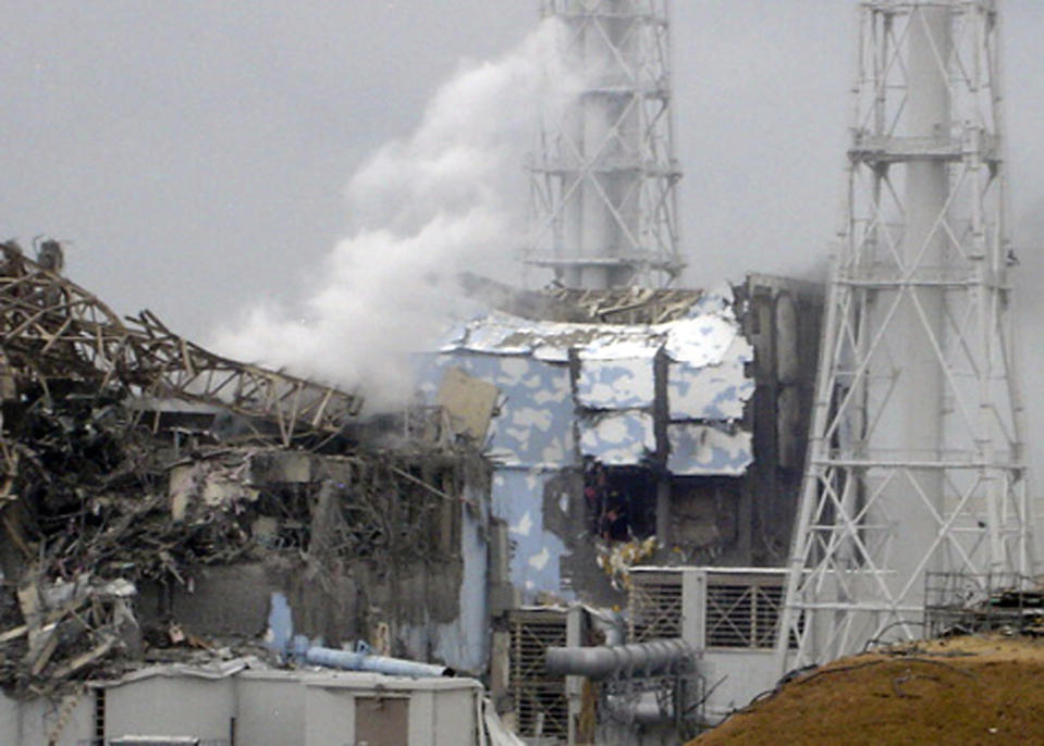 FILE - In this March 15, 2011 file photo released by Tokyo Electric Power Co. (TEPCO), smoke rises from the badly damaged Unit 3 reactor, left, next to the Unit 4 reactor covered by an outer wall at the Fukushima Dai-ichi nuclear complex in Okuma town, northeastern Japan. Japan's crippled nuclear power plant is struggling to find space to store tens of thousands of tons of highly contaminated water used to cool its broken reactors. Up to 200,000 tons of radioactive water - enough to fill more than 50 Olympic-sized swimming pools - are being stored in hundreds of gigantic tanks built around the Fukushima Dai-ichi plant. The amount is expected to more than triple within three years, mainly because ground water is leaking into damaged reactor buildings. (AP Photo/Tokyo Electric Power Co., File) EDITORIAL USE ONLY