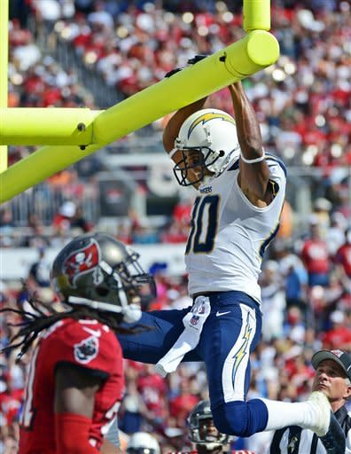 San Diego Chargers wide receiver Malcom Floyd (80) hangs on the goal post in front of Tampa Bay Buccaneers cornerback E.J. Biggers (31) after scoring on a three-yard, second quarter touchdown during an NFL football game, Sunday, Nov. 11, 2012, in Tampa, Fla. (AP Photo/Phelan M. Ebenhack)