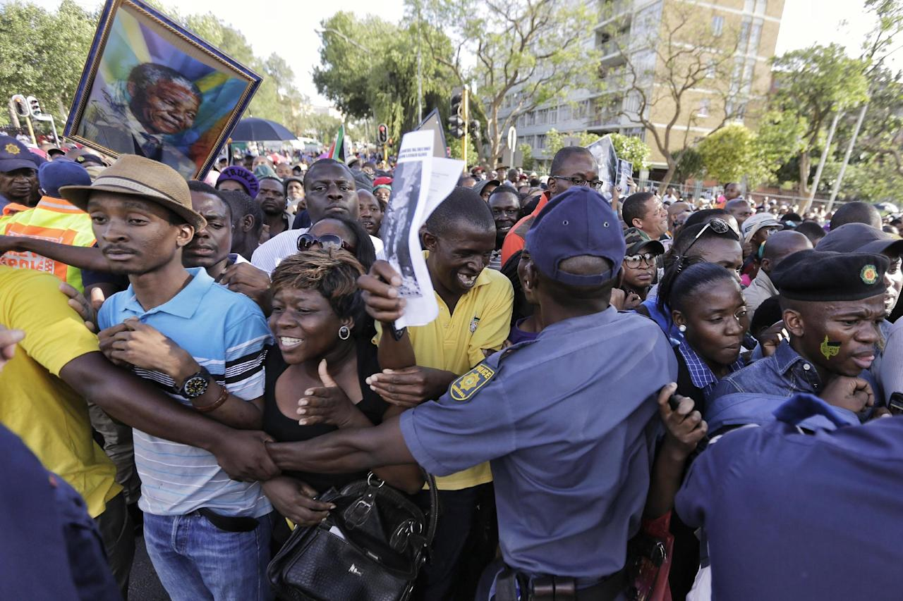 Police officers try to control the crowd after they announced they would reopen the entrance to the Union Buildings to pay their respects to Nelson Mandela, in Pretoria, South Africa, Friday, Dec. 13, 2013. Former South African President Nelson Mandela is on the third and final day of lying in state at the Union Buildings in Pretoria. (AP Photo/Markus Schreiber)