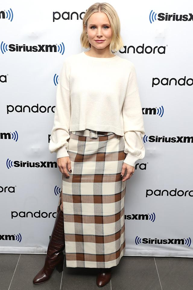 wears a cream balloon-sleeve sweater and a plaid skirt with a side slit revealing brown croc-embossed boots at SiriusXM Studios in N.Y.C.