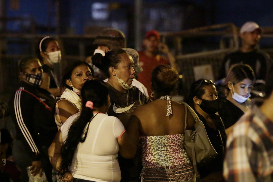 Relatives of inmates wait for news outside the Litoral penitentiary after a riot, in Guayaquil, Ecuador, Tuesday, Sept. 28, 2021. A police and military operation managed to regain control of the regional prison after five hours, according to a statement from Ecuador's prison service, but reported at least 24 dead and 48 injured during the riot. (AP Photo/Angel DeJesus)