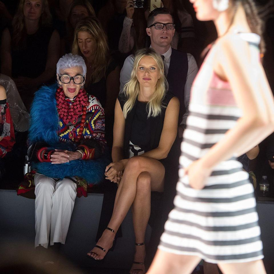 <p>Iris attends a New York Fashion Week show wearing white pants, cerulean fur, and a plethora of costume jewelry and bangles. <br></p>