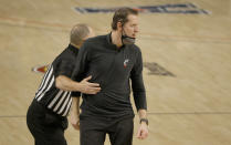 Cincinnati head coach John Brannen is pulled back toward the team bench by a game official as Cincinnati plays Wichita State during the second half of an NCAA college basketball game in the semifinal round of the American Athletic Conference men's tournament Saturday, March 13, 2021, in Fort Worth, Texas. (AP Photo/Ron Jenkins)