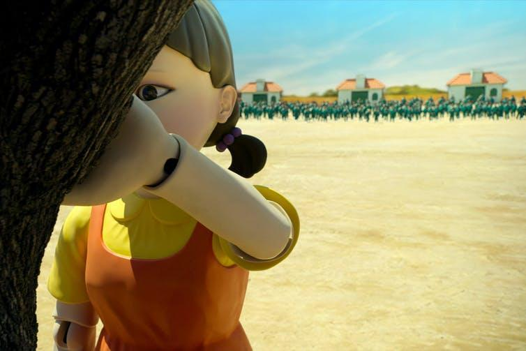 In the foreground, a large robotic figure of a girl faces a tree. In the distance, hundreds of people in matching green tracksuits are gathered.