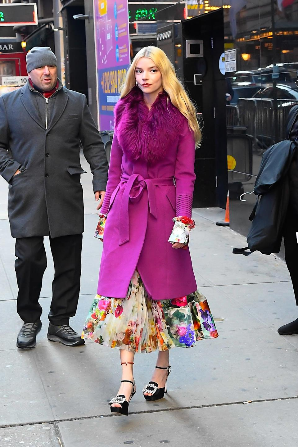 <p>Anya played up the magenta blooms on her pleated dress with this furry-collared coat in NYC. And how could we skip over her accessories: hoop earrings, embellished buckle platforms, and a beaded anklet. </p>